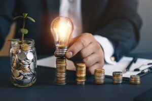 Business man hand holding light bulb on money stack.