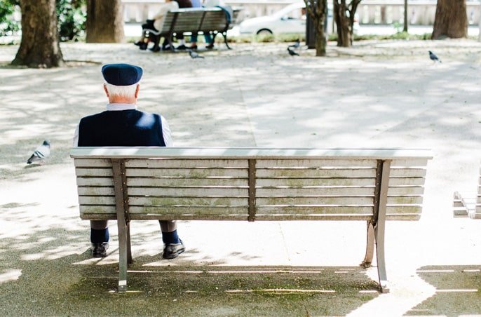 Elderly man sitting alone on a bench.